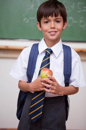 Portrait of a schoolboy holding an apple in a classroom photo