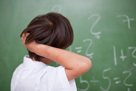 scratching head: Schoolboy thinking while scratching the back of his head in front of a chalkboard