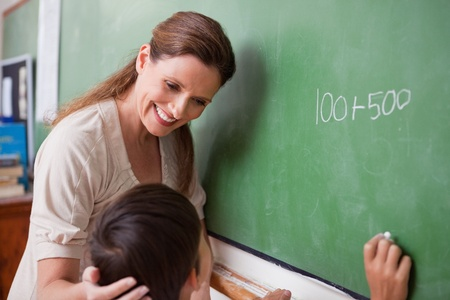 Smiling schoolteacher helping a schoolboy doing an addition on a blackboard photo