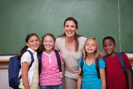 Schoolteacher posing with her pupils in a classroom photo