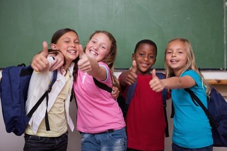 positiveness: Los compa�eros de clase posando con el pulgar hacia arriba en un aula Foto de archivo