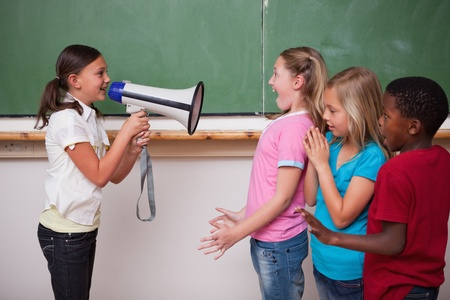 Schoolgirl screaming through a megaphone to her classmates in a classroom photo