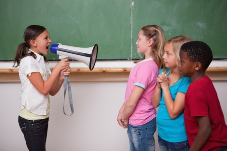 Angry schoolgirl screaming through a megaphone to her classmates in a classroom photo