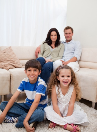 family sofa: Cheerful family sitting in the living room Stock Photo