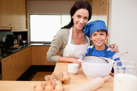 Mother and son preparing cake together photo