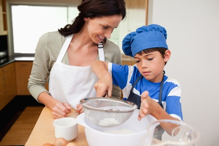 Son and mother preparing dough together photo