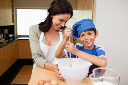 Mother and son having fun preparing a cake together photo