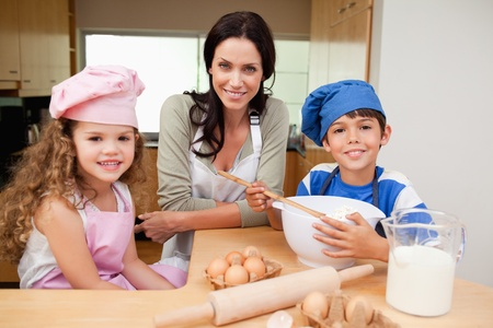 Mother and her children preparing cake together Stock Photo - 11682896