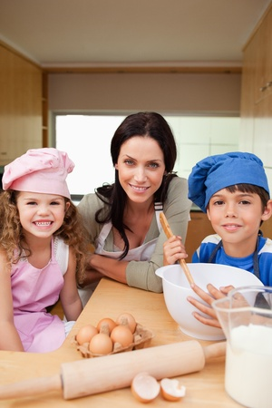 Mother and her children preparing dough together Stock Photo - 11681516