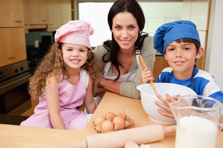 Mother and her children preparing cookies together Stock Photo - 11682479