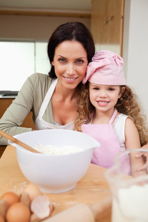 Mother and daughter preparing cake together photo