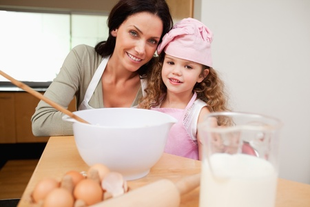 Mother and daughter preparing dough together photo