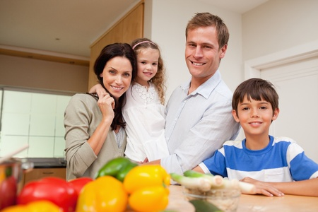 Family standing in the kitchen together photo