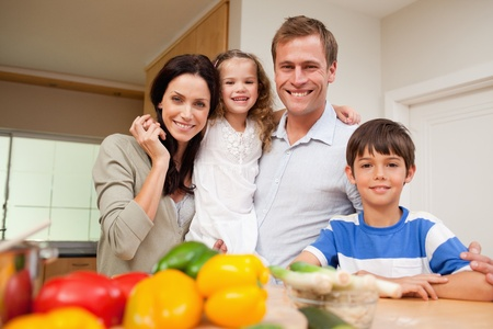 Happy family standing in the kitchen together photo