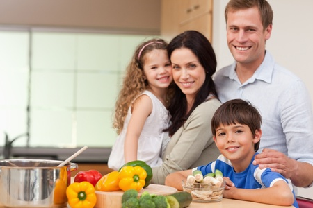 meal preparation: Smiling family standing in the kitchen together Stock Photo
