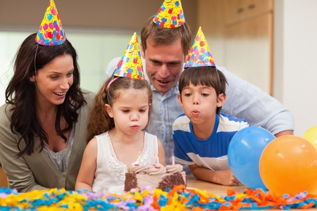 blow out: Young boy helping his little sister to blow out the candles on her birthday cake Stock Photo