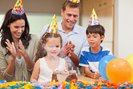 Parents applauding her little daughter who just blew out the candles on birthday cake photo