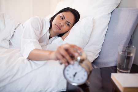 Young woman annoyed by ringing alarm clock Stock Photo