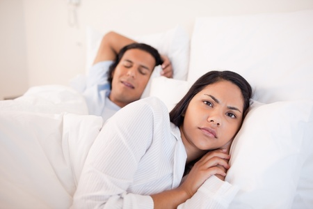 Young woman lying awake next to her sleeping boyfriend photo