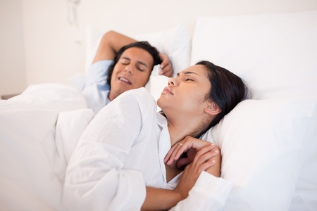 woken: Young woman being woken up by snoring boyfriend Stock Photo