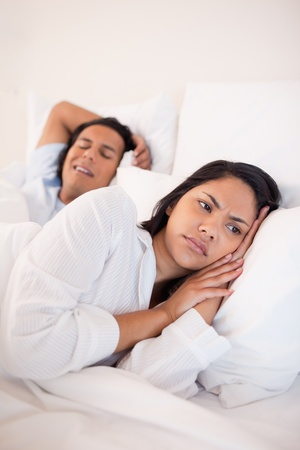 Displeased young woman lying next to snoring boyfriend photo