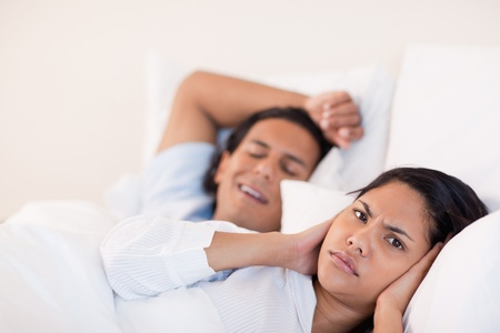 Young man waking his girlfriend with snoring photo