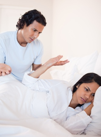 Young couple having a dispute in the bed photo