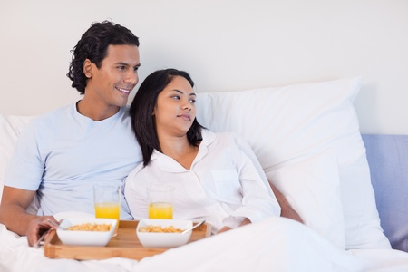 Young couple having breakfast in the bed photo