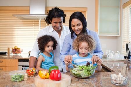 Young family preparing salad together in the kitchen photo