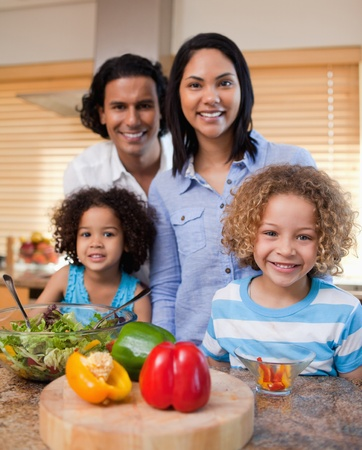 Young family with salad together in the kitchen photo