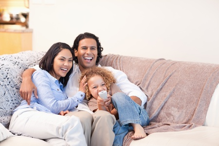 Happy young family watching television together photo