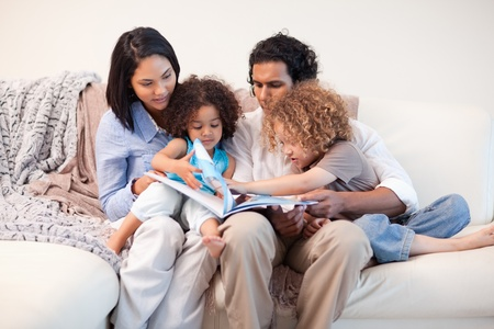 Young family on the sofa looking at the photo album together Stock Photo - 11683884