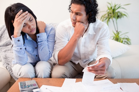 Frustrated young couple checking their bills photo