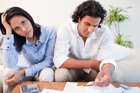 Sad young couple checking their bills Stock Photo - 11682974