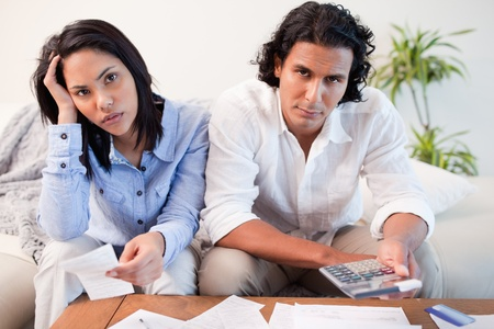 money issues: Young couple calculating their costs