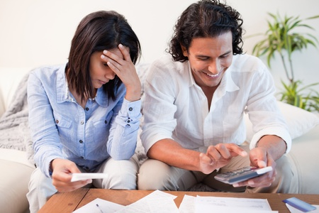 Young couple checking their bills in the living room Stock Photo - 11683350