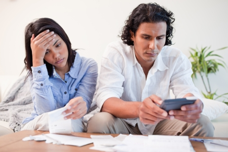 financial problems: Young couple checking bills