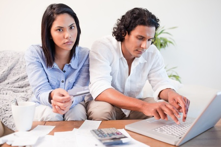 bank accounts: Young couple checking their bank accounts online in the living room