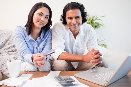 Young couple doing online banking in the living room Stock Photo - 11684067
