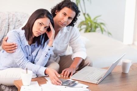 persona deprimida: Pareja joven teniendo dificultades para pagar sus facturas