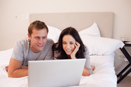 Young couple using laptop on the bed together photo