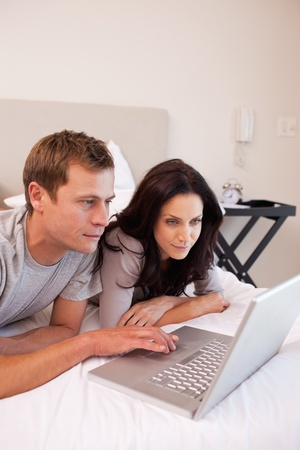 Young couple using laptop in the bedroom together photo
