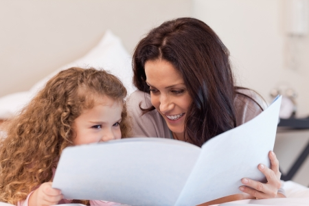 Young mother and daughter reading a book together photo