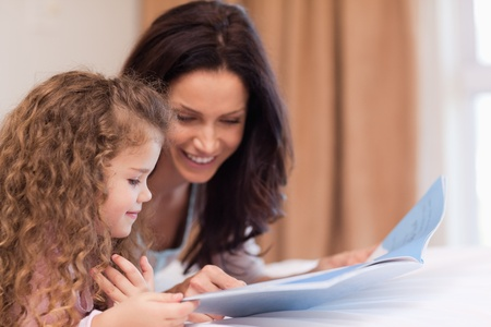Side view of young mother and daughter reading a book together photo