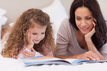 bedtime story: Little girl reading bedtime story with her young mother Stock Photo