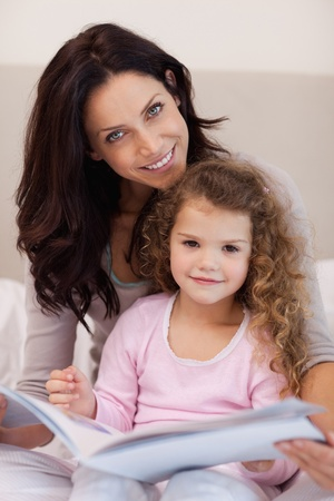 Smiling young mother reading a bedtime story with her little daughter photo