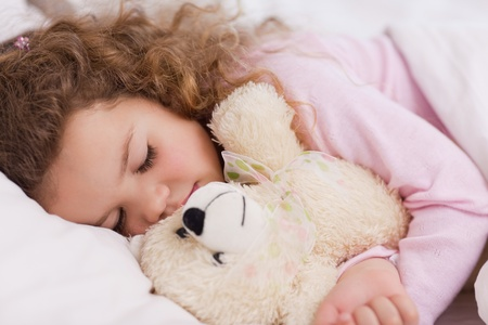 Little girl hugging her teddy while sleeping photo