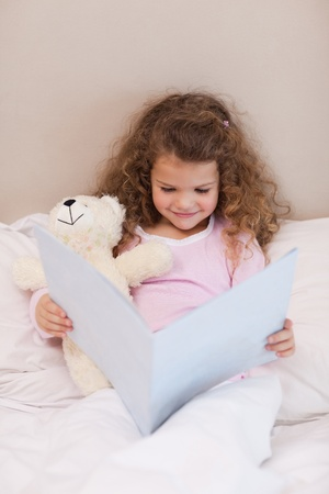Smiling little girl reading a book photo