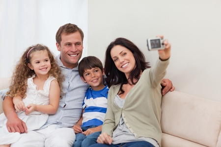 Young mother taking family photograph on the couch photo