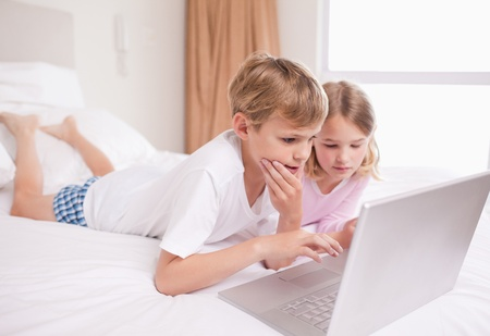 Children using a laptop in a bedroom photo